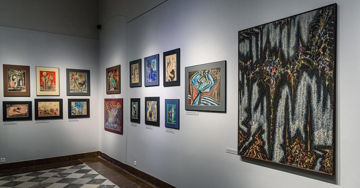 Fragment ekspozycji muzeum, na białych ścianach wiszą obrazy w stylu abstrakcyjnym.