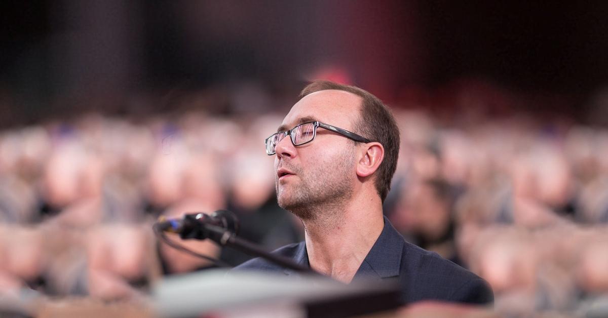 Mężczyzna lirycznie odgrywa koncert na scenie, za nim widać rozmytą publiczność.