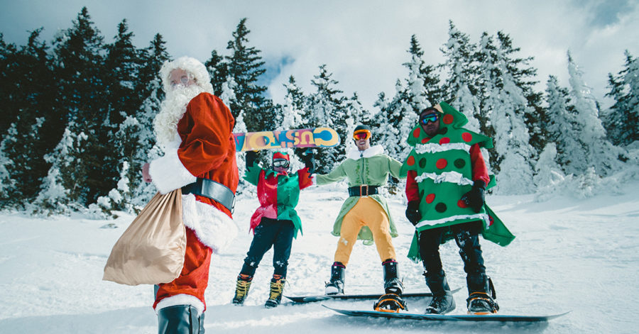 Święty Mikołaj i jego pomocnicy zjeżdżają na snowboardzie, po zaśnieżonym stoku.