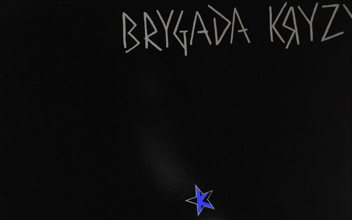 """Okładka albumu, na czarnym tle znajduje się biały kontur gwiazd pięcioramiennej, w jej środku jest listera: """"K"""". Na górze znajduje się napis: """"Brygada Kryzys"""" stworzony z prostych kresek."""