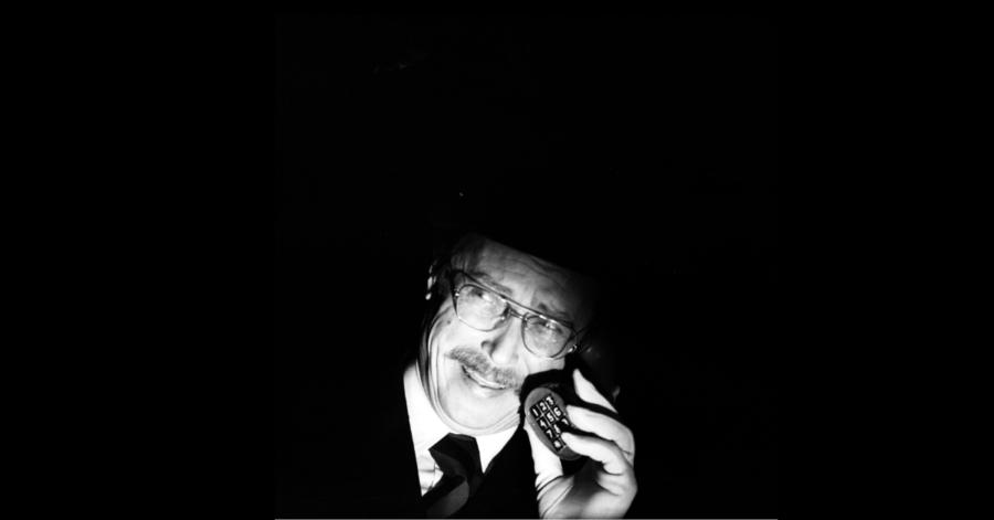 Oświetlona twarz mężczyzny rozmawiającego przez telefon, reszta zdjęcia jest czarna.