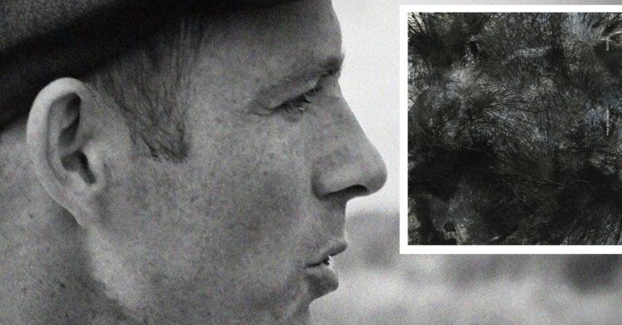Twarz mężczyzny z profilu na rozmytym tle. Obok niego znajduje się kwadrat w środku znajduje się abstrakcyjna grafika, która przypomina rozwianą wysoką trawę, sfotografowaną od góry.