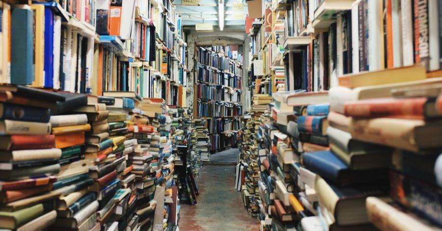 Korytarz pomiędzy półkami przepełnionymi książkami.