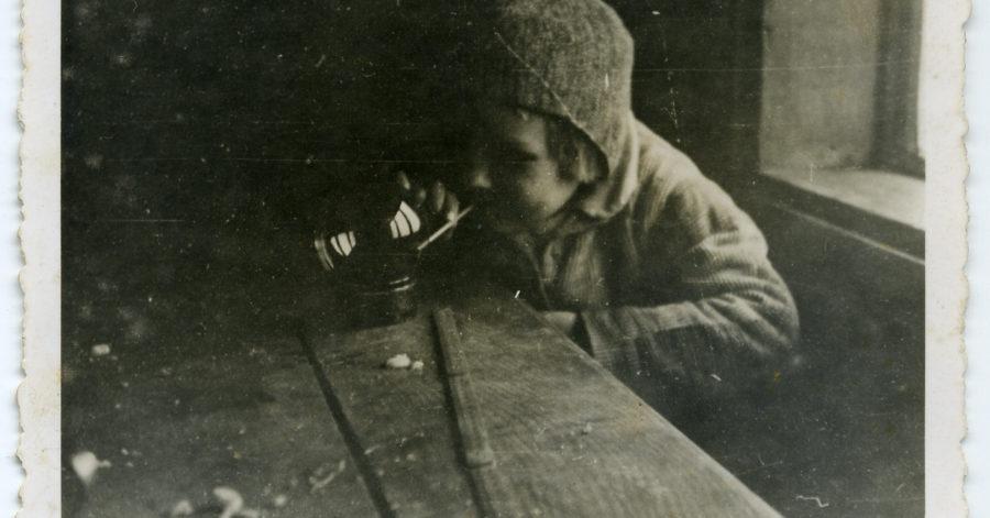 Stara wyblakła fotografia przedstawia chłopczyka, który przegląda się w szklanej kuli, ustawionej na stole. W ustach ma cienką rurkę, którą trzyma palcami, jakby palił papierosa.