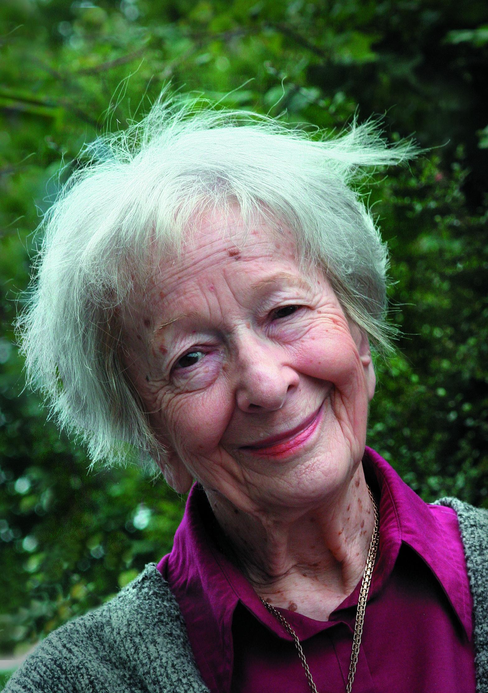 Portret przedstawia uśmiechniętą starszą kobietę, która stoi na zielonej roślinności.