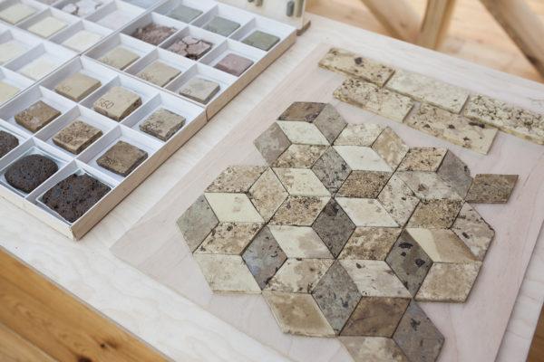 Na stole leży pudełko, z kwadratowymi próbkami kamiennych materiałów, opisanych odciśniętą na nich liczbą. Obok leży deska z mozaiką płaskich kamieni, wyglądająca sześciany ułożone na sobie.