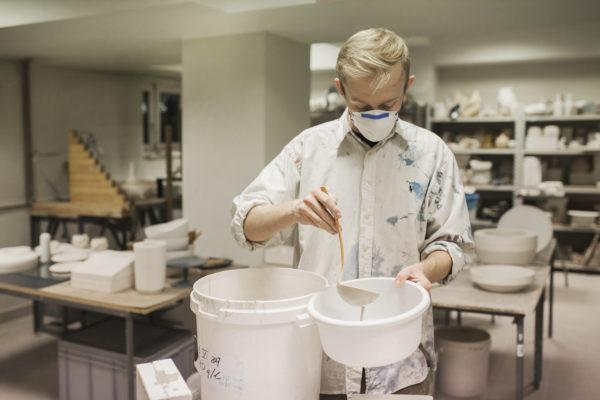 Mężczyzna w fartuchu i maseczce wlewa oleistą ciecz do miski za pomocą chochli.