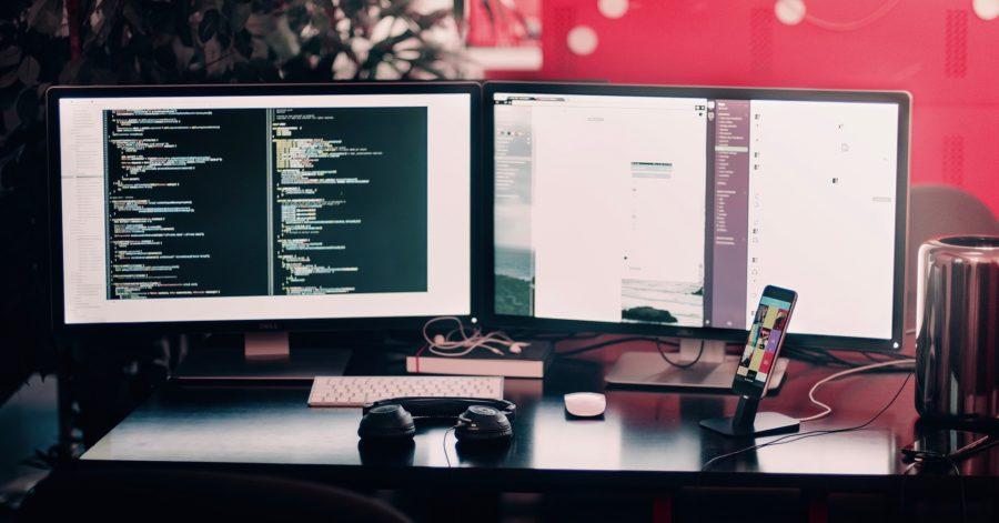 Na biurku stoją dwa włączone monitory, wyświetlające coś innego, obok na podstawce stoi włączony smartfon.
