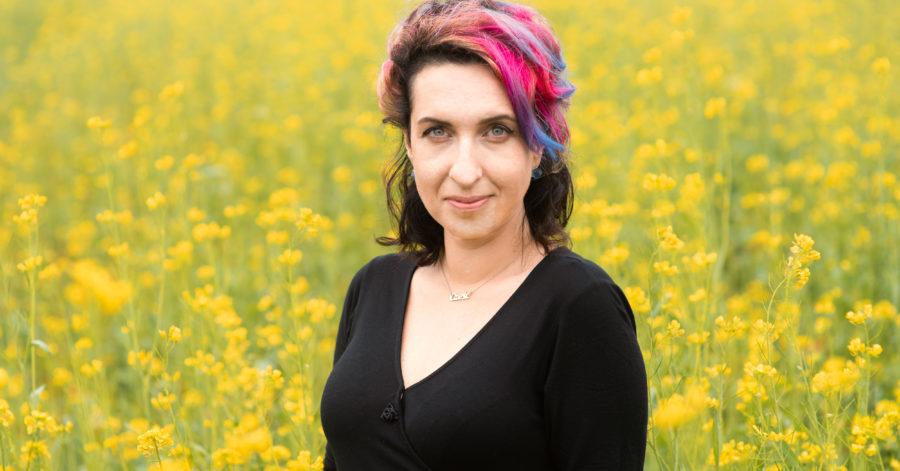 Uśmiechnięta kobieta stoi na polu wysokich żółtych kwiatów. Jej włosy są pomalowane na różne kolory.