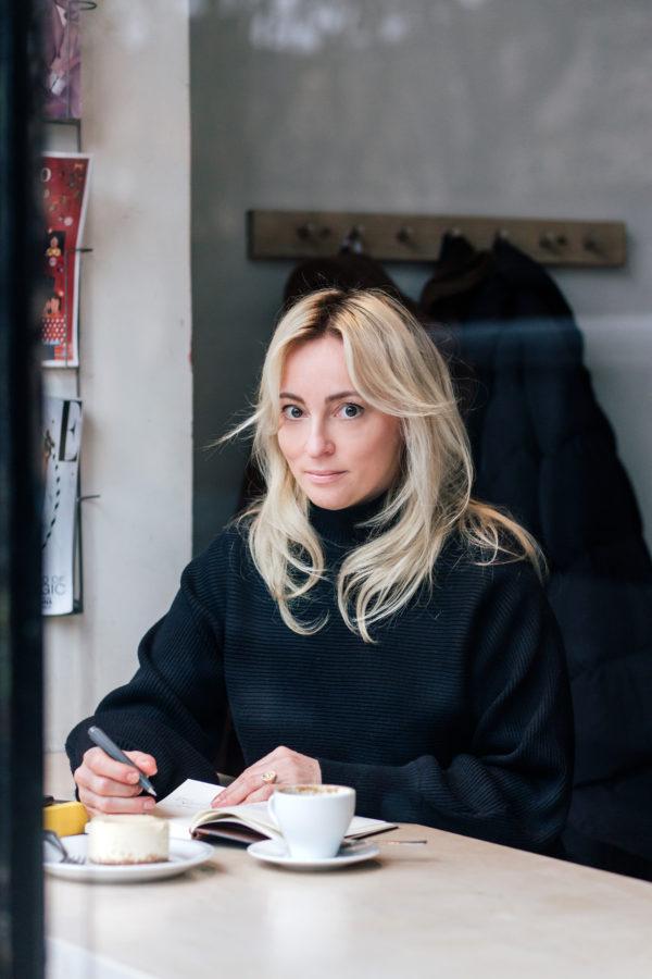 Młoda kobieta siedzi przy stoliku z kawą i pisze coś w notatniku.