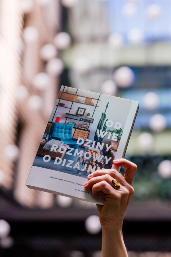 """Książka: """"Odwiedziny. Rozmowy o dizajnie"""", trzymana w dłoni na rozmytym kolorowym tle zdjęcia."""