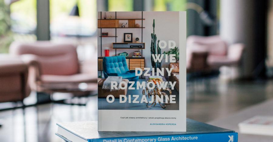 """Na okładce książki znajduje się fragment urządzonego pokoju oraz biały napis: Odwiedziny. Rozmowy od dizajnie"""". Książka ustawiona jest pionowo, na leżący książkach o fotografii, znajdujących się na stoliku w kawiarni."""