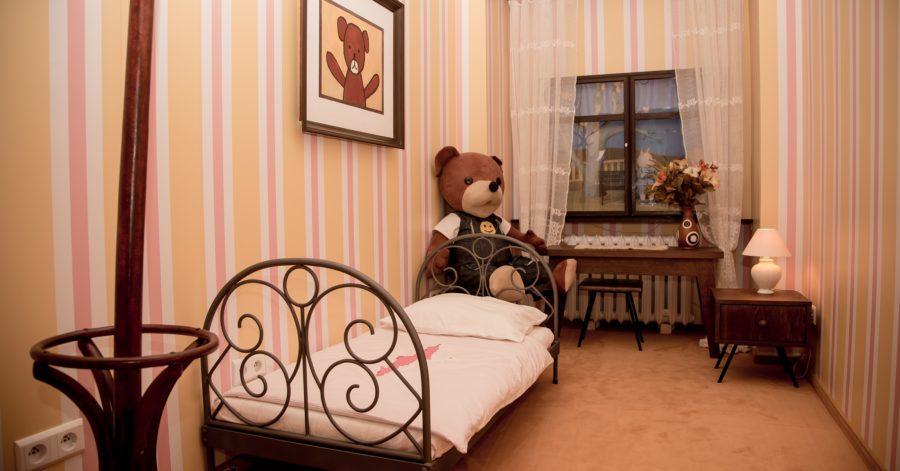 Pluszowy miś siedzi na krześle w swoim pokoju.