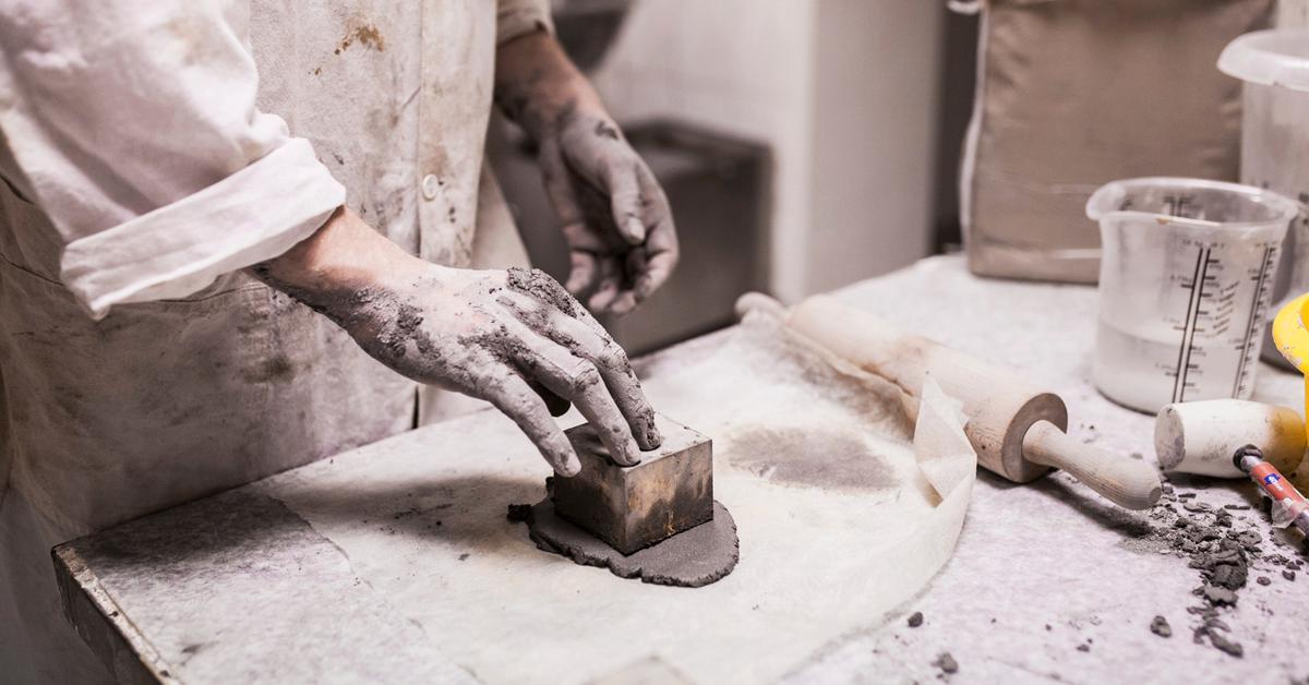 Człowiek w brudnym fartuchu, wycina kształt w gliniastym rozwałkowanym materiale, za pomocą formy w kształcie sześcianu.