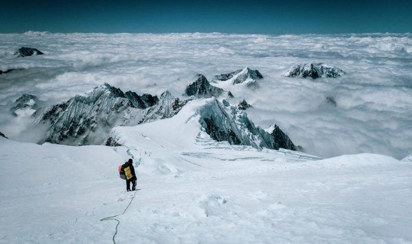 Człowiek schodzący z ośnieżonego szczytu, większość gór przed nim jest zasłonięta przez grube chmury. Miejscami wystają czubki szczytów.