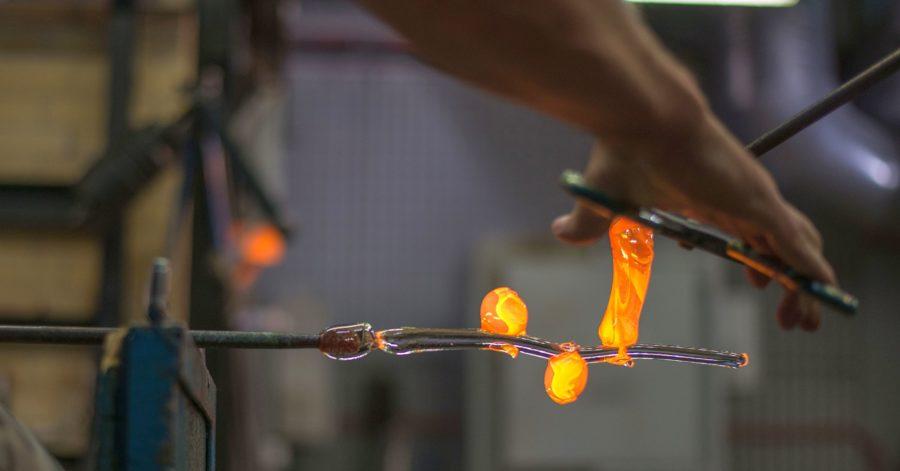 Mężczyzna podgrzewa palnikiem zakończenia dwóch szklanych form, które trzyma w dłoniach. Jedna forma ma kształt kwiatu, a druga łodygi.