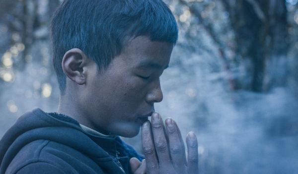 Chłopiec modli się z zamkniętymi oczami. Jego złożone dłonie dotykają jego ust.