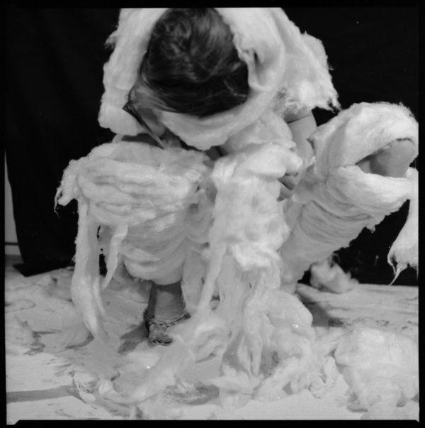 Kobieta owinięta watą, kuca z pochyloną głową w dół.