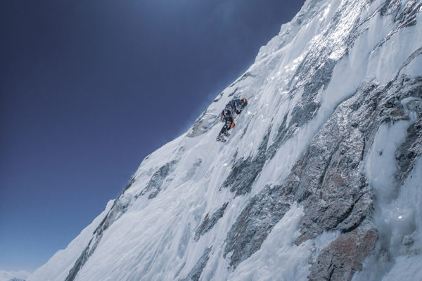 Człowiek wspina się po prawie pionowej ścianie szczytu, w większości pokrytej lodem.