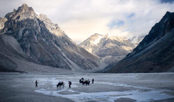 Grupa ludzi wraz z osłami trzymającymi na plecach ich dobytek, przeprawiają się przez przełęcz.