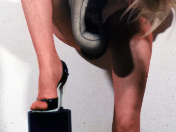 Nogi kobiety, w krótkiej spódniczce, z namalowaną kreską na tylnej stronie nogi, imitującą rajstopy. Prawa noga ustawiona jest prowokacyjnie na podwyższeniu.