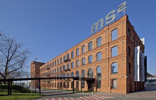 """Industrialny budynek z czerwonej cegły, na jego dachu przymocowane są wielkie metalowe znaki: """"MS do kwadratu""""."""