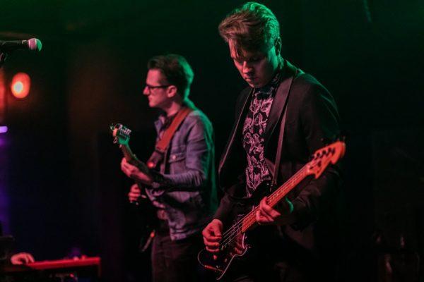 Na pierwszym planie Stefan Nowakowski daje koncert na gitarze basowej, na drugim planie Łukasz Borowicki gra na gitarze elektrycznej.