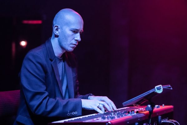 Mężczyzna gra na klawiszach na scenie.
