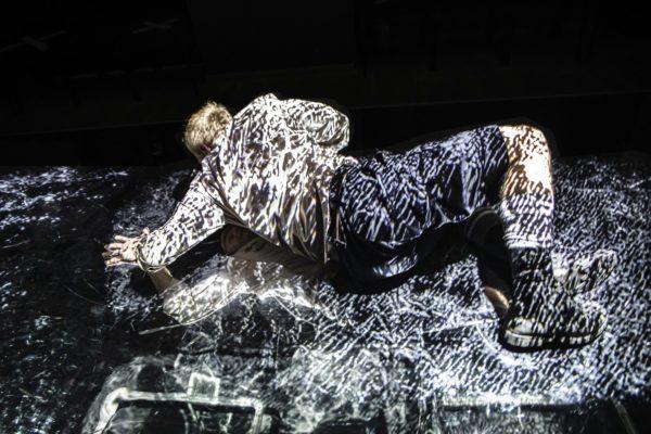 Mężczyzna leży na scenie, patrzy się na swoje odbicie w podłodze. Scena oświetlona jest mocnym światłem tworzącym jasne kształty.