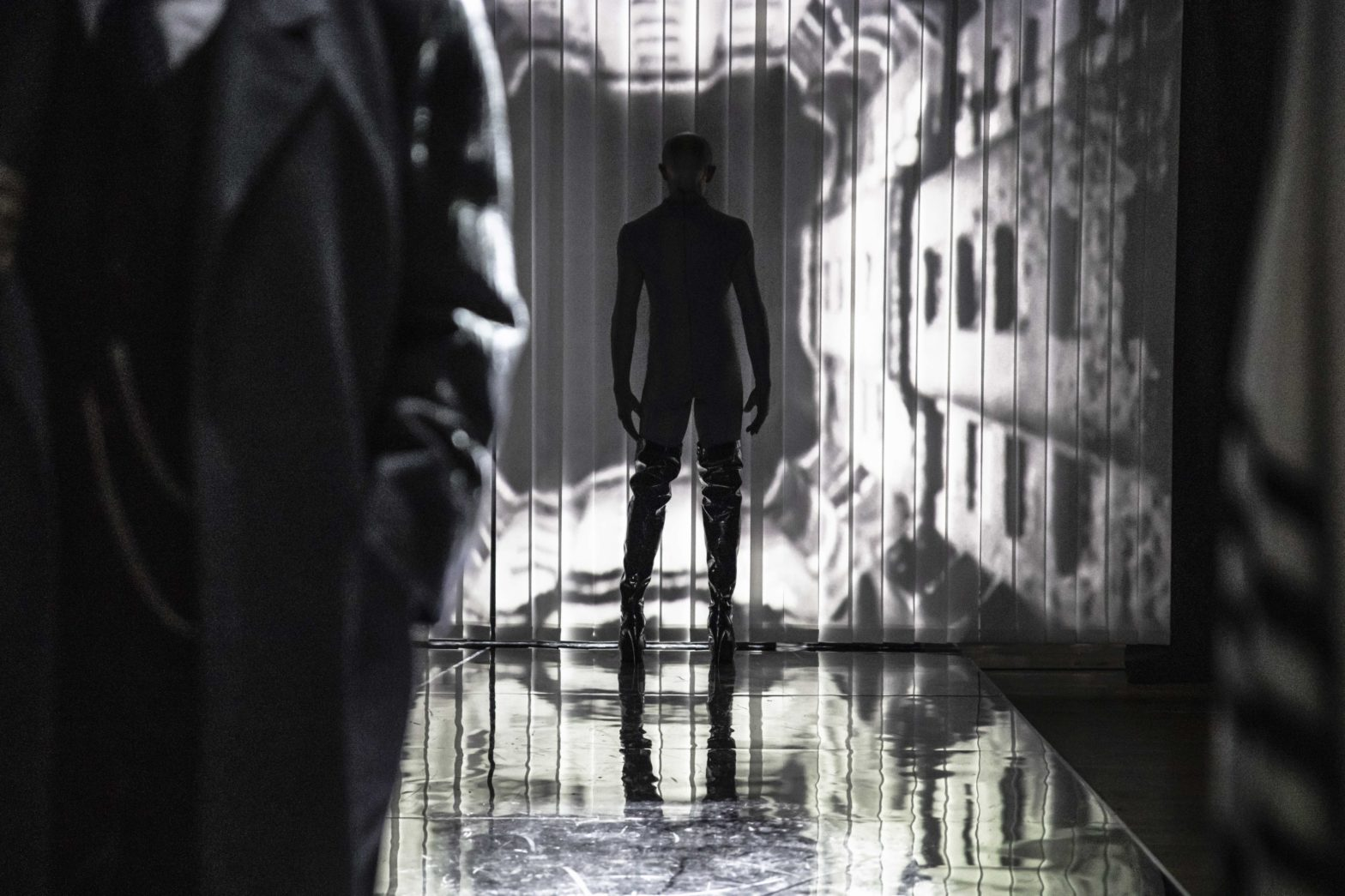 Scena spektaklu, odwrócony mężczyzna w czarnym kostiumie stoi naprzeciwko ściany, na której jest wyświetlony tunel. Na pierwszym stoi mężczyzna w długim płaszczu.