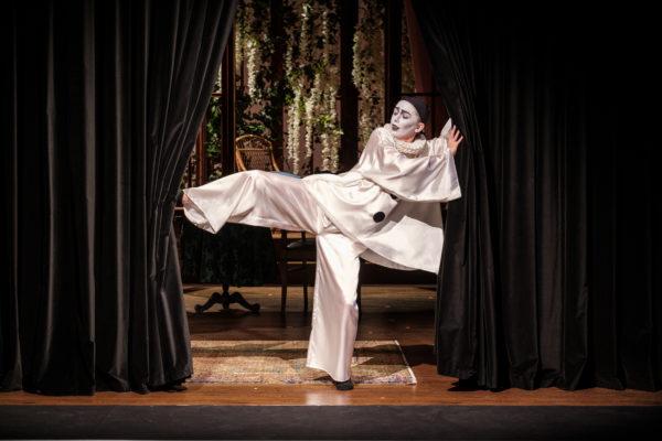 Scena spektaklu, człowiek w makijażu mima trzyma kurtynę, aby nie zasłoniła sceny. Człowiek stoi na jednej nodze, drugą nogą trzyma lewą stronę kurtyny, a rękami - prawą.