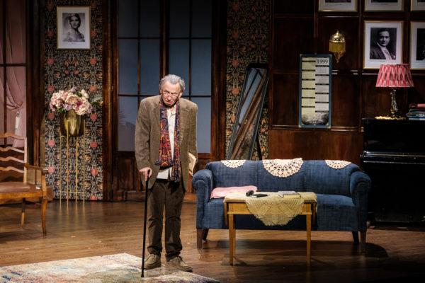 Scena spektaklu, starszy elegancko ubrany mężczyzna stoi wspierając się laską. Zwraca się do publiczności.