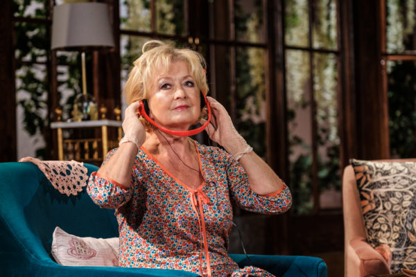 Scena spektaklu, starsza kobieta słucha czegoś na słuchawkach. Słuchawki przytrzymuje rękami, gdyż są one skierowane w dół.