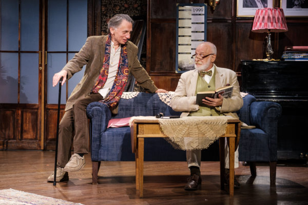 Scena spektaklu, starszy mężczyzna z laską siedzi na krawędzi kanapy. Mówi do drugiego starszego mężczyzny siedzącego na kanapie z książką.