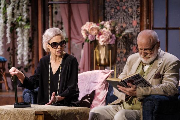 Scena spektaklu, starsza kobieta z laską siedzi mówi do starszego mężczyzny, który jest zajęty czytaniem książki.