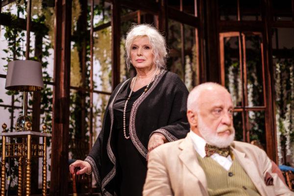 Scena spektaklu, starsza kobieta stoi wyprostowana, opiera się jedną ręką o laskę, drugą o krzesło, na którym siedzi zamyślony starszy mężczyzna. Aktorzy patrzą się w różne strony.