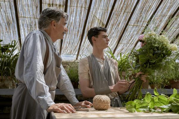 """Fotos z filmu """"Szarlatan"""". Starszy mężczyzna przygląda się, jak młody mężczyzna robi bukiet kwiatów."""