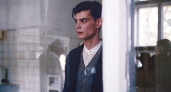 """Fotos z filmu """"Szarlatan"""". Młody mężczyzna przygląda się czemuś nieujętemu w kadrze."""