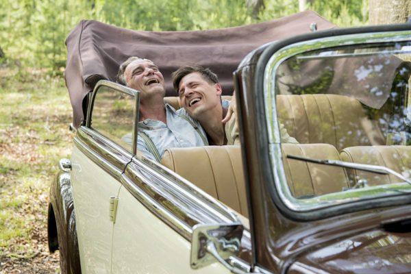 """Fotos z filmu """"Szarlatan"""". Dwójka mężczyzn w średnim wieku, na tylnym siedzeniu eleganckiego kabrioletu, śmieje się jednocześnie tuląc się o siebie."""