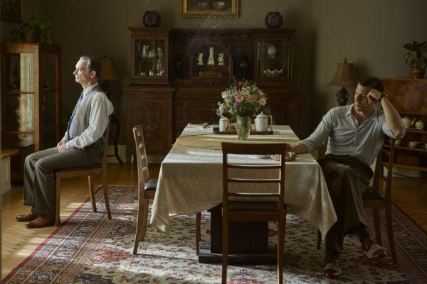 """Fotos z filmu """"Szarlatan"""". Dwójka zamyślonych mężczyzn. Po lewej starszy mężczyzna siedzi na krześle przed oknem i wygląda przez nie. Młodszy mężczyzna siedzi przy stole i pali papierosa."""