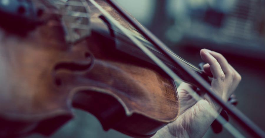 Zbliżenie skrzypiec, smyczek na strunie i dłoń na gryfie, wskazuje, że ktoś na nich gra.