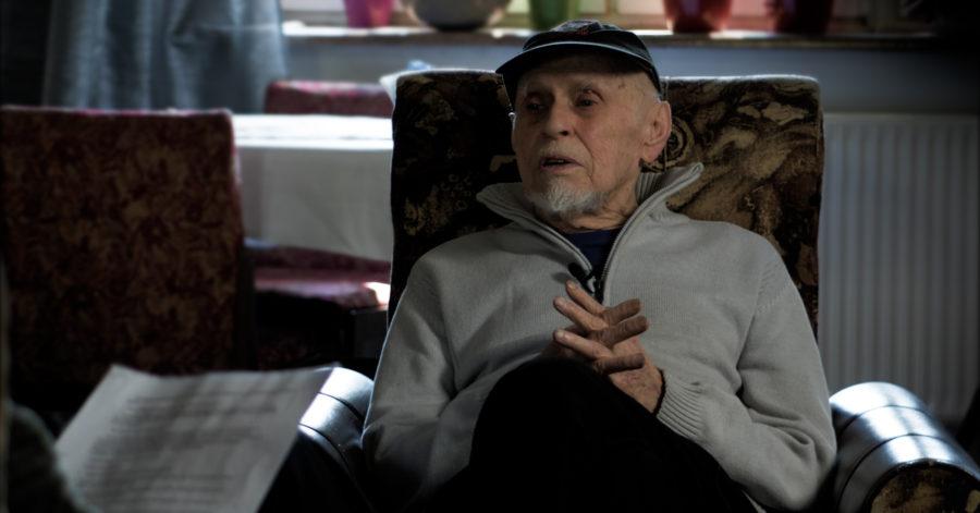 Starszy mężczyzna siedzi na fotelu i udziela wywiadu.