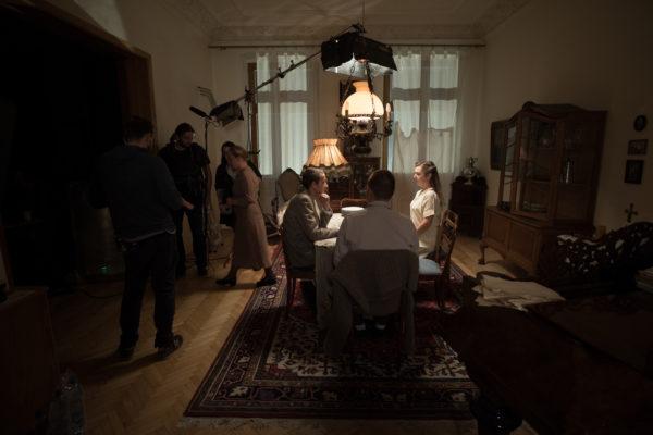 """Kulisy powstawania filmu """"Położna z Auschwitz"""". Trzech dorosłych siedzi przy stole. Nad nimi znajduje się lampa filmowa. Z lewej strony stoi kilku członków ekipy filmowej."""