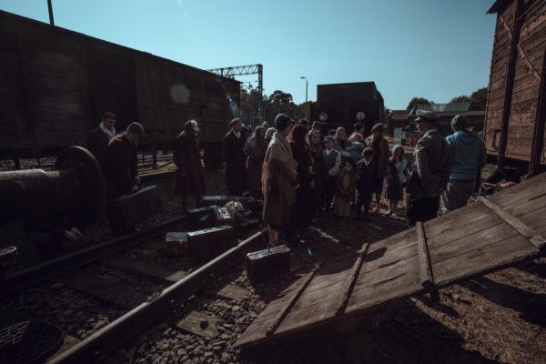 """Kadr z filmu """"Położna z Auschwitz"""". Tłum ludzi czeka przy pociągu towarowym."""