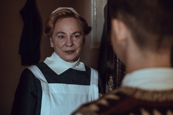 """Kadr z filmu """"Położna z Auschwitz"""". Starsza kobieta w fartuchu otwiera drzwi wejściowe młodemu mężczyźnie."""