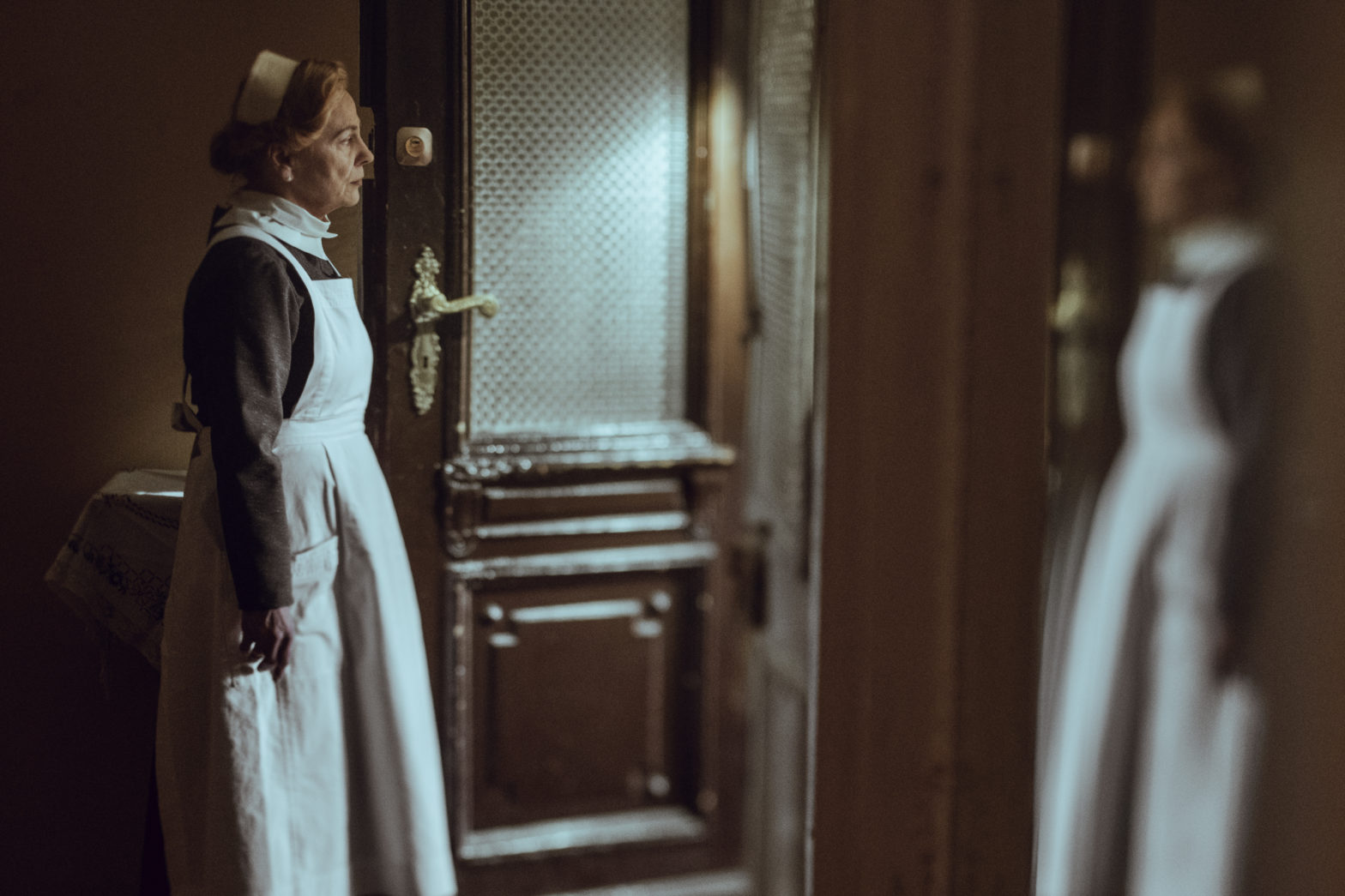 """Kadr z filmu """"Położna z Auschwitz"""". Starsza kobieta w fartuchu otwiera komuś drzwi wejściowe."""