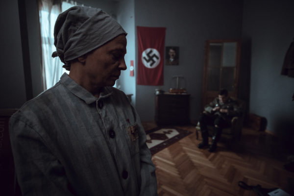 Kadr z filmu. Gabinet oficera Trzeciej Rzeszy. Mężczyzna w mundurze siedzi na krześle. Na pierwszym planie stoi starsza kobieta w więziennym pasiaku.