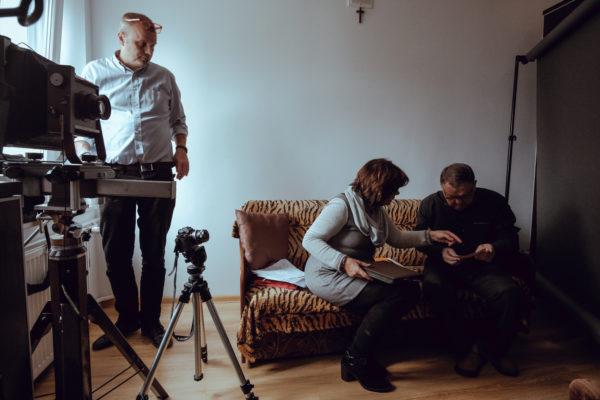 Kulisy powstawania filmu. Kobieta i mężczyzna siedzą na kanapie i przeglądają zdjęcia z albumu. Z boku przygląda im się mężczyzna, stojący nieopodal kamer filmowych na statywach.