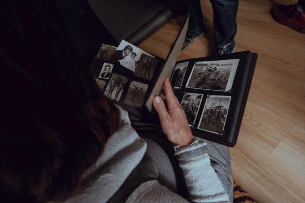 Otwarty album ze starymi zdjęciami, który przegląda kobieta.