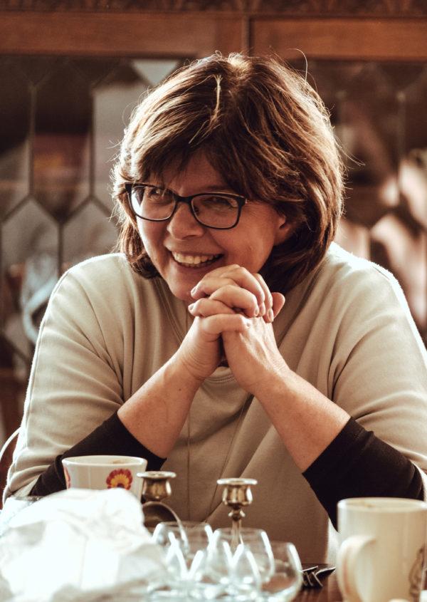 Uśmiechnięta kobieta w średnim wieku siedzi przy stole. Ma włosy do ramion, na nosie ma okulary.